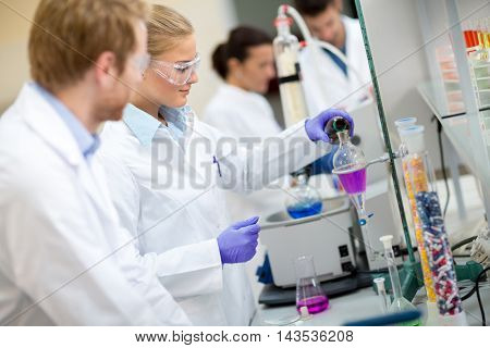 Female chemical technician mixing fluids in laboratory