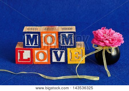 The words mom love spelled with alphabet blocks against a blue background with a pink rose