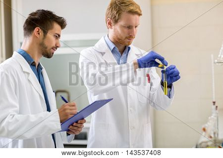 Laboratory technician mixing liquids in lab while assistant write data