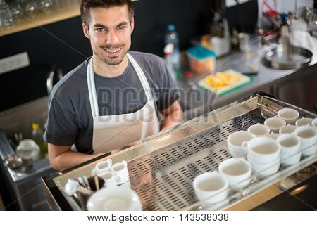 Portrait of a barista leaning on the coffee machine at the coffee shop