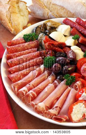 Platter of antipasti appetizers, with crusty bread.