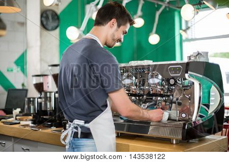 With backs male barista making coffee and serving coffee