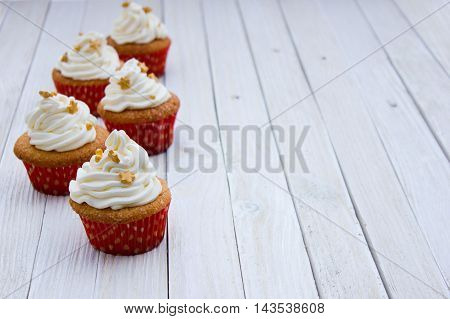 Cupcakes with mascarpone cream and gold decoration on a white wooden table. Sweets for a birthday a party