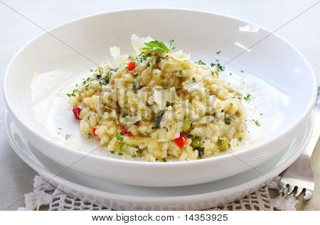 Chicken and garlic risotto, garnished with shaved parmesan and parsley.