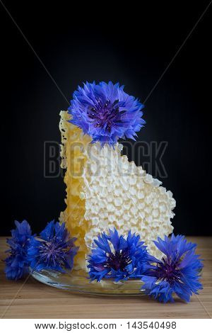 Honey in honeycomb with blue flowers on black background
