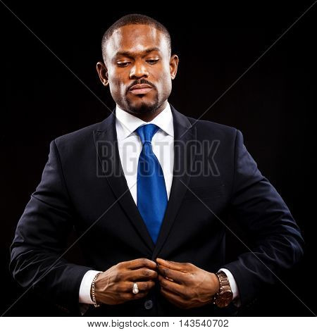 African business man isolated on black adjusting his jacket