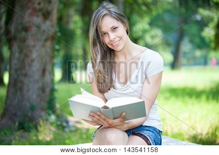 Portrait of a smiling woman sitting on a bench in a park