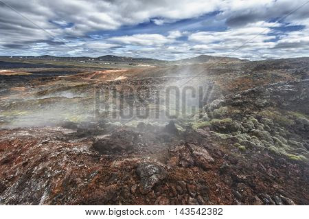 Inhospitable dramatic volcanic landscape full of steam at Krafla geothermal area, Iceland