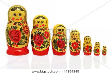Russian Babushka nesting dolls, isolated on white.  Reflected on glass surface.