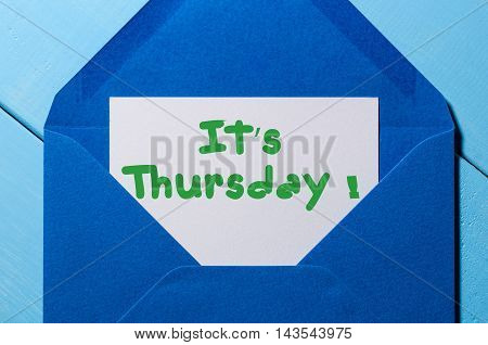 The words It's Thursday written on a peace of paper in blue envelope. Happy week concept.