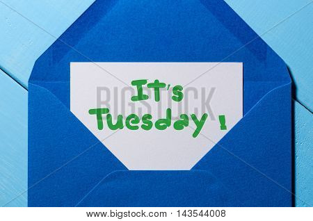 The words It's Tuesday written on a peace of paper in blue envelope. Happy week concept.