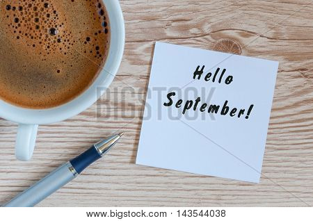 Hello September wrote at paper sticker with coffee and pen on wooden background.