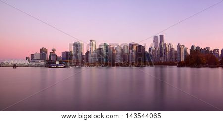 Vancouver downtown architecture and boat with water reflections at sunset panorama