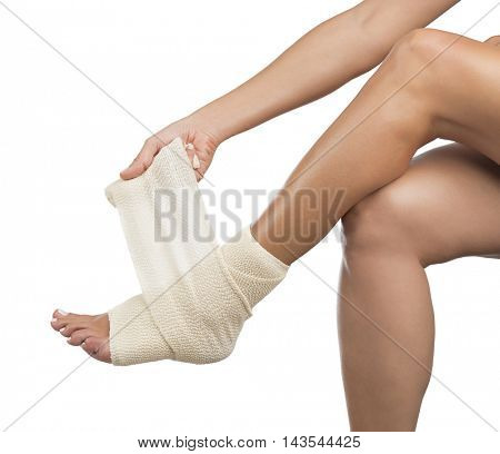 Woman wrapping her foot with bandage on a white background.