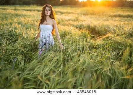 Sensual girl stands in the rye field and looks to the side on the sunset background. Woman touches the rye. She wears a light dress with prints of flowers.