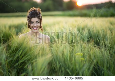 Joyous girl sits in the rye field and looks to the side with a smile on the sunset background. She holds her hands together.  Outdoors. Horizontal.