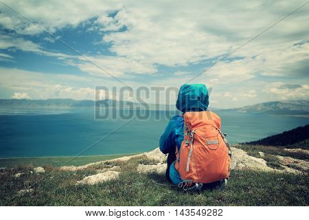 young woman hiker sit on mountain peak