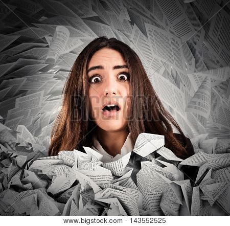 Shocked businesswoman submerged by the working documents