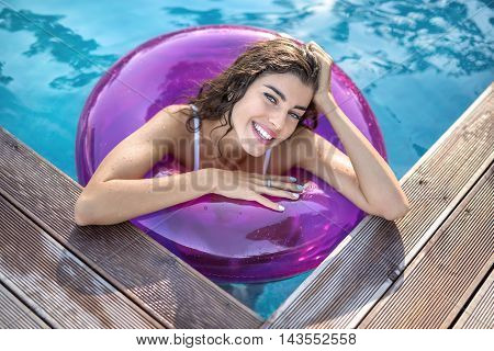 Charming model with wet hair in a white swimsuit in the purple rubber ring in the swimming pool looks into the camera with a smile. She holds the right hand on the ring, left hand is on the head.