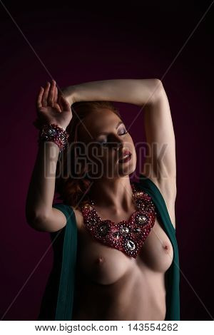 Erotica and chic. Topless redhead woman posing in jewelry