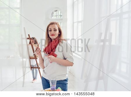 woman artist paints on workshop indoor with little girl on background