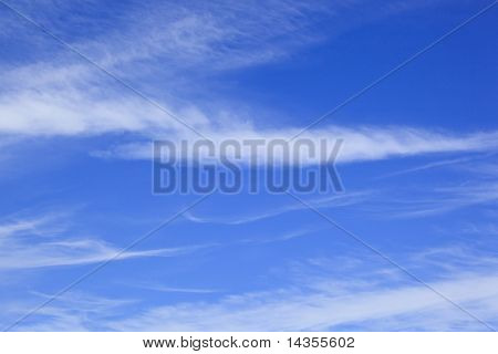 Blue sky with scattered white clouds.