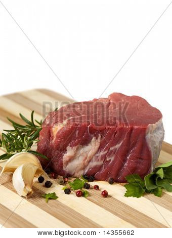 Best cut of raw beef filet steak, with garlic cloves, peppercorns and herbs.