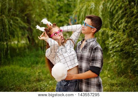 Sweethearts teenagers eat cotton candy and fool around. Girlfriend and boyfriend together. They wear glasses. She made the ears of cotton candy. First love. He falls in love. Date.