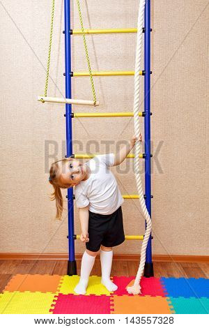 Little girl holding a rope. Wall bars. Sports Equipment. Children's sports.