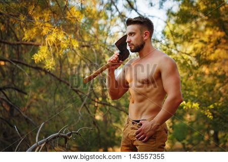 Lumberjack holds a cleaver. Woodcutter with naked torso in the coniferous forest. Felling trees. Logging. Manual labor. Brutal man.
