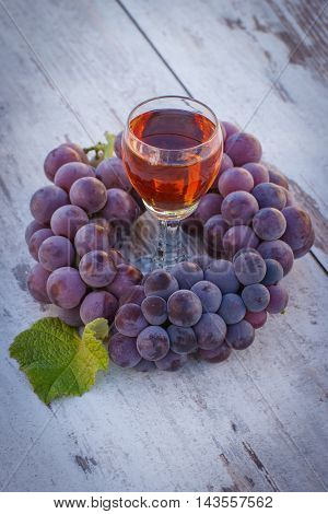 Grapes With Leaf And Glass Of Wine On Wooden Table In Garden