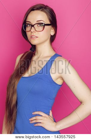 young pretty woman in hipster glasses smiling on pink background, fashion teacher