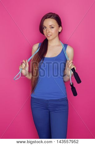 young happy slim girl with skipping rope on pink background smiling sweety cute, glamour sport wear