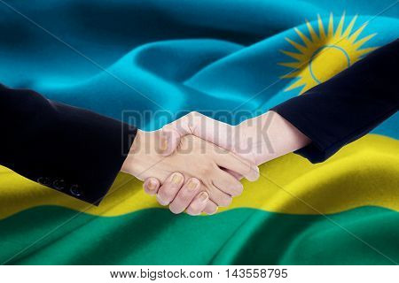 Photo of two entrepreneur hands in a business suit closing a meeting by shaking hands with a Rwanda flag background