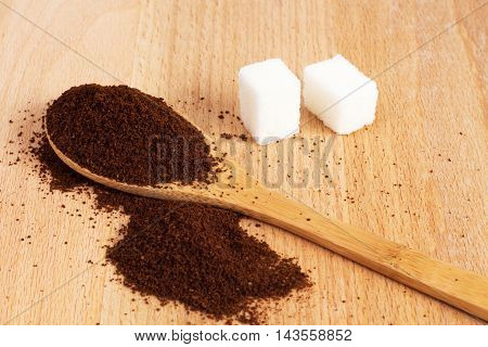 sugar ground coffee in a wooden spoon on the table