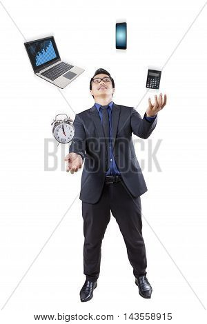Young businessman juggling in the studio with business items like laptop cellphone calculator and alarm clock