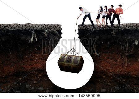 Picture of young entrepreneurs work together to get a treasure chest in the soil isolated on white background