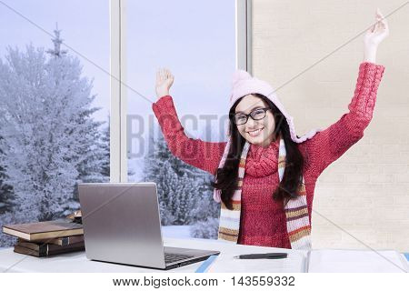 Photo of a cheerful female high school student raising hands while studying with laptop and wearing winter clothes