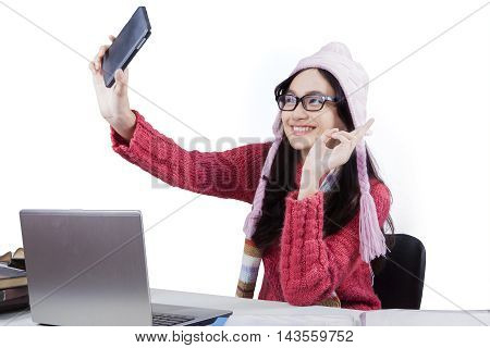 Happy female high school student wearing sweater and taking selfie picture while studying with laptop