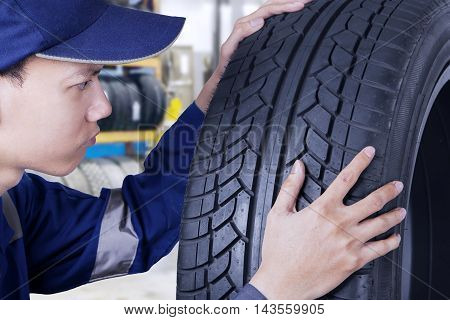 Picture of a professional mechanic checking a new tyre while wearing uniform in the workshop