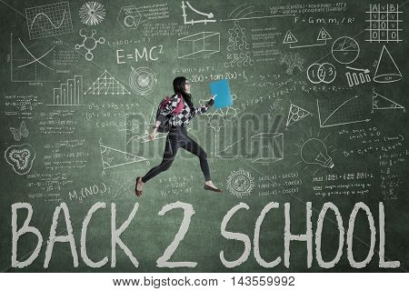 Image of high school student carrying bag and jumping in the class with text of Back to School on the chalkboard