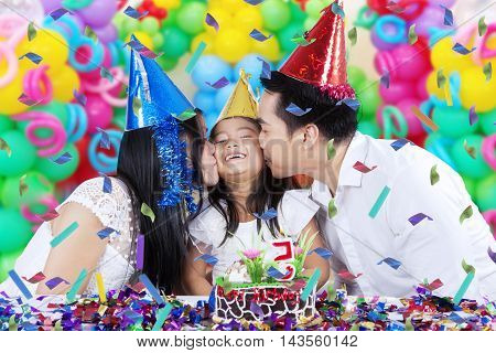 Portrait of a cheerful little girl kissed by her parents while celebrating birthday party