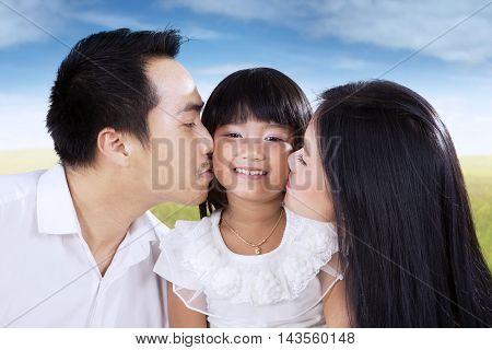 Photo of happy little girl kissed by her parents while smiling at the camera shot on the meadow