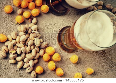 Glasses of beer, cheese balls and pistachio nuts