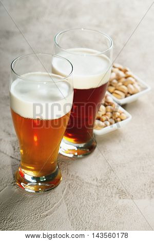 Glasses of fresh beer and pistachio nuts