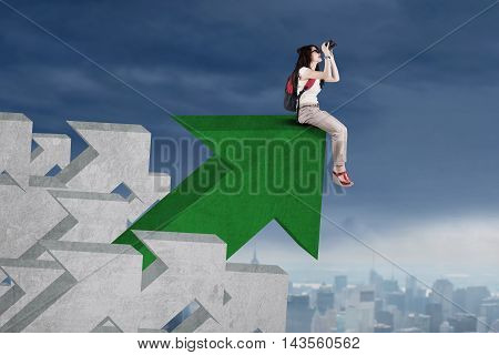 Female high school student sitting on the upward arrow and look at the sky with binoculars