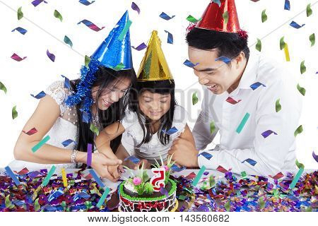 Portrait of happy little girl and her parents cut birthday cake together isolated on white background