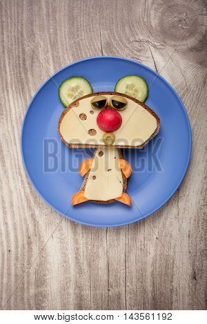 Funny bear made of bread and cheese on plate and desk