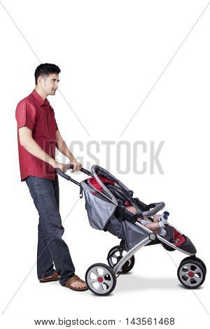 Full length of young man pushing his son with a stroller in the studio isolated on white background