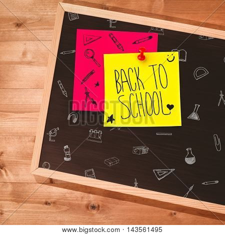 Back to school message against small blackboard on wooden floor